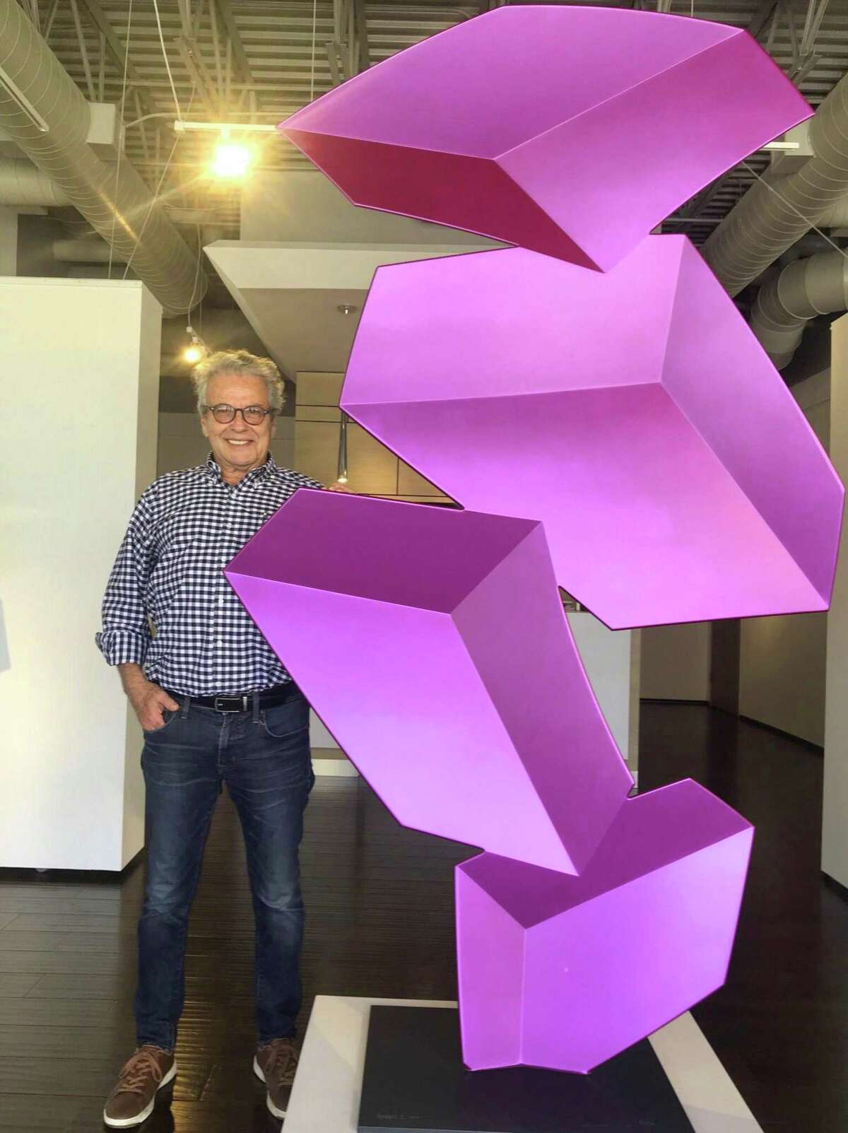 """Artist Rafael Barrios poses with """"Apocalipsis,"""" one of his large """"virtual volume"""" sculptures, at Art of the World Gallery."""