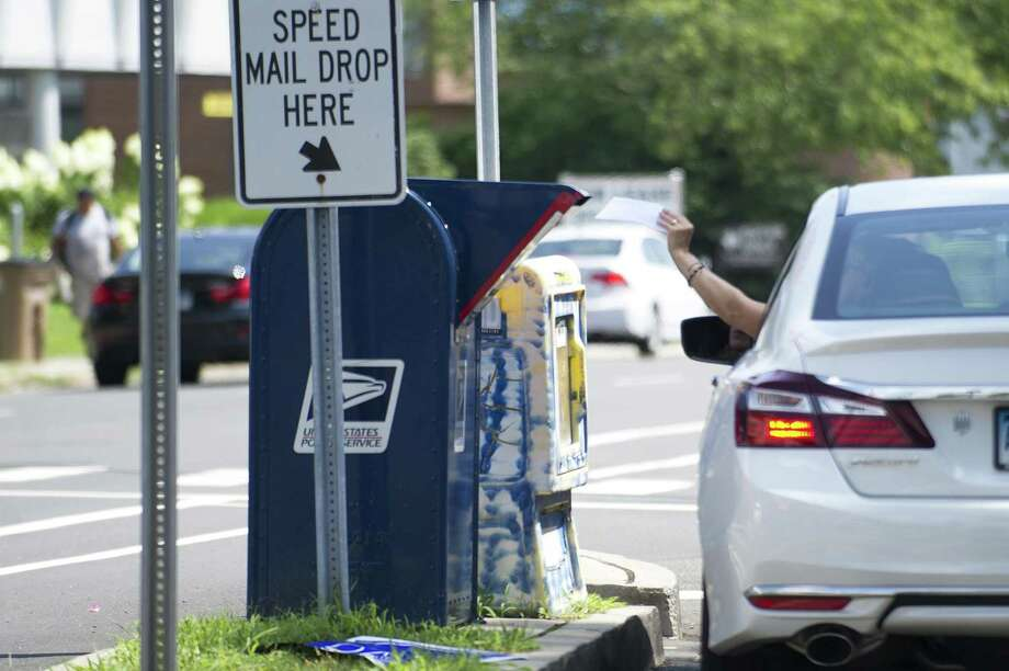 A woman drops a letter into the mailbox across the street from Ridgeway Shopping Center on Summer St. in Stamford, Conn. on Tuesday, Aug. 14, 2018. That mailbox has been victimized by thiefs who used sticky paper and string to fish letters out, including tax payments and checks. Photo: Michael Cummo / Hearst Connecticut Media / Stamford Advocate