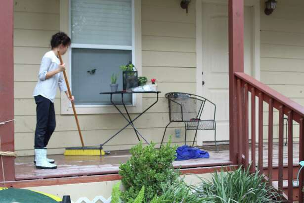 Katelynn Velazquez uses a push broom to help her parents, Gabby Velasquez and Gustavo Velasquez, with clean-up efforts for their flooded home on Meeks Road in Humble on Wednesday, Aug. 30.