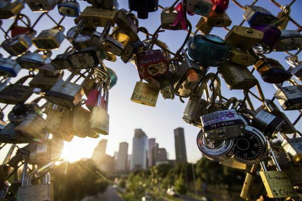 View of the skyline of Houston surrounded by love locks on the pedestrian bridge over Allen Parkway