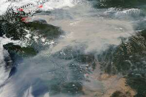 """The satellite photo below, taken Tuesday, shows the red """"hot spots"""" marking the large areas of fire in B.C. Fires in Washington can also be seen to the south."""