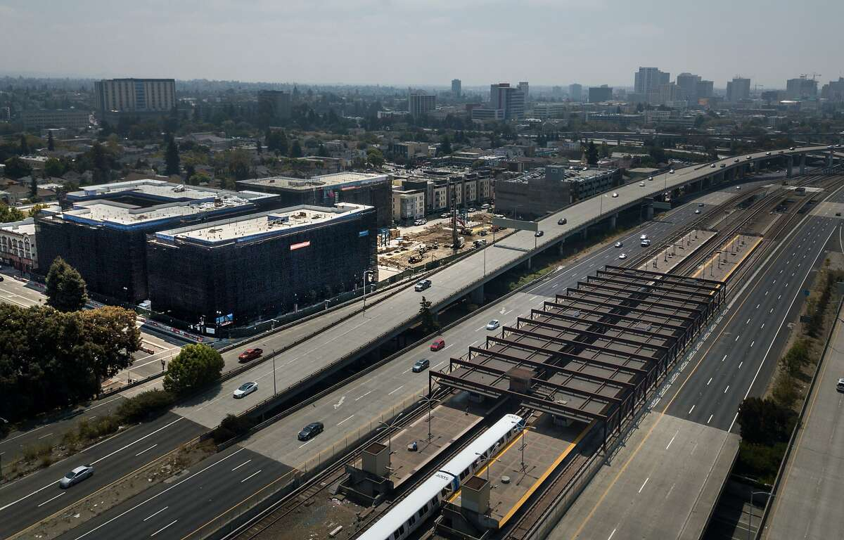 A large apartment building and plaza (left) is being constructed next to the MacArthur BART station on Wednesday, Aug. 15, 2018 in Oakland, Calif.