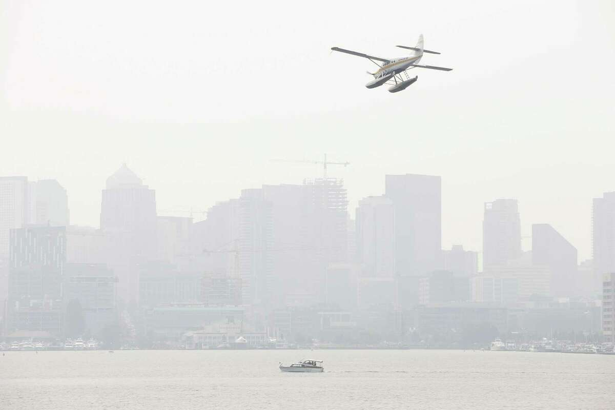 Wildfire smoke causes a thick haze over the Seattle skyline and unhealthy air quality levels, Wednesday, Aug. 15, 2018.