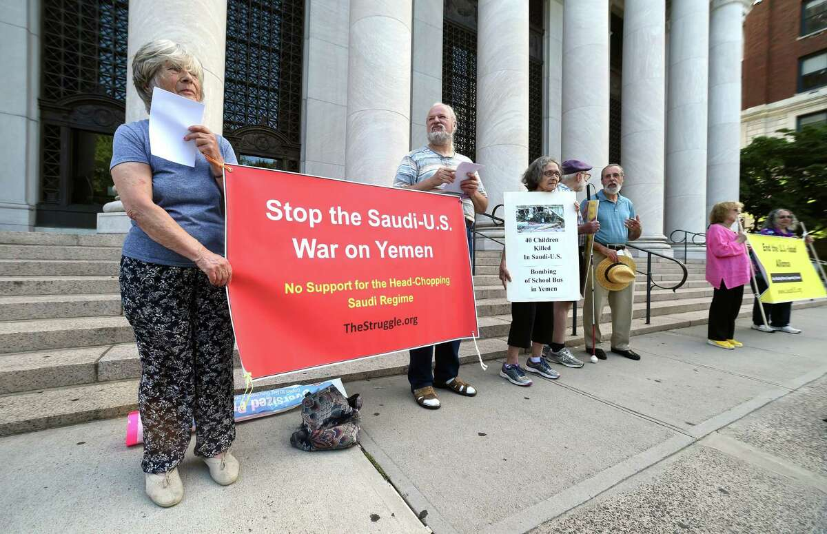 Julia Berger, left, and Frank Panzarella, center, join others on the Middle East Crisis Committee to protest the Saudi bombing of a school bus in Yemen, in front of the federal courthouse in New Haven Wednesday.