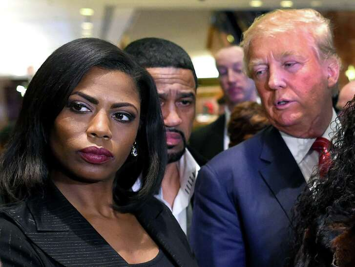 Omarosa Manigault Newman, left, appears alongside Republican presidential hopeful Donald Trump during a press conference that followed Trump's meeting with African-American religious leaders in New York Dec. 1, 2015. She has now turned on Trump, writing a tell-all book.