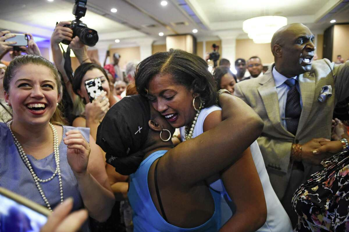 Jahana Hayes, center right, and her husband, Milford, right, make their way through the crowd of supporters after winning the Democratic primary for the Connecticut's 5th Congressional District against Mary Glassman, Tuesday, Aug. 14, 2018, in Waterbury, Conn.