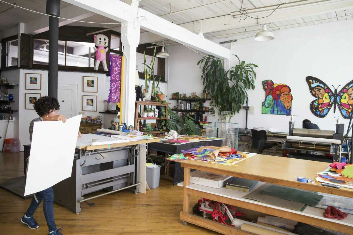 Artist Favianna Rodriguez prepares a new canvas to create a new collage piece at her studio space in Oakland.