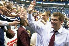 UConn coach Geno Auriemma and star Diana Taurasi greet fans after the Huskies won their third straight NCAA championship in 2004.