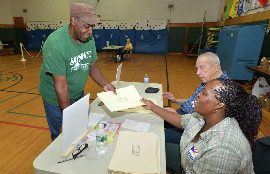 Ernie Dumas checks in and takes a ballot at District 140b, Columbus Magnet School, during voting on Tuesday in Norwalk. Photo: Alex Von Kleydorff / Hearst Connecticut Media / Norwalk Hour