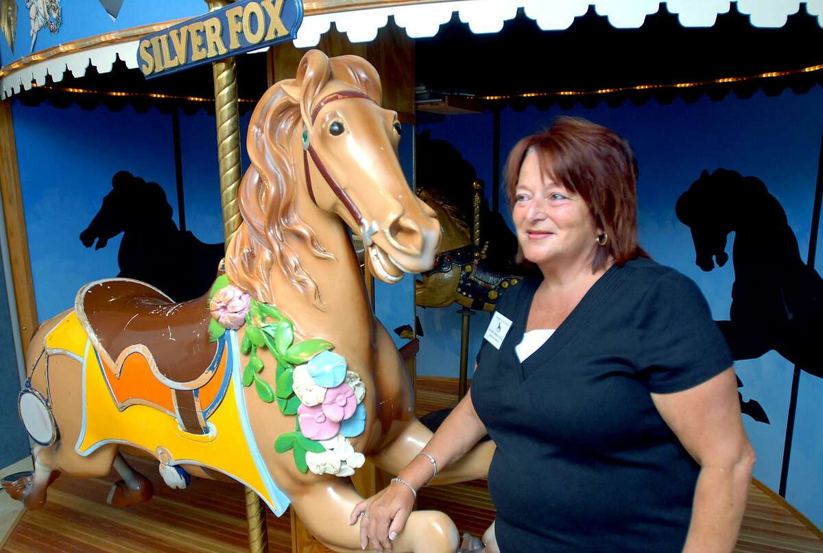 wh-savin rock-aqg-9/9/08 Natalie Guiliano DeRosa of West Haven is photographed next to Silver Fox, one of the original Savin Rock carousel horses, at the Savin Rock Conference Center in West Haven on 9/9/2008. Photo by Arnold Gold AG0275C