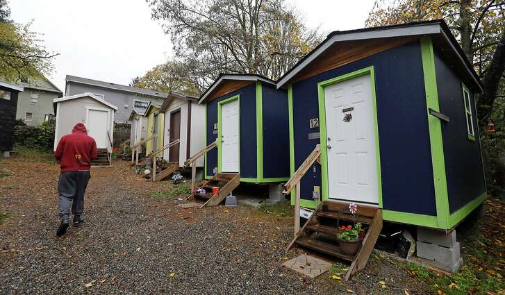 In this photo taken Thursday, Nov. 9, 2017, a resident walks past a row of tiny houses at a homeless encampment in Seattle where full size homes stand behind. Tiny homes could be the solution to all kinds of housing needs, offering warmth and security for the homeless, an affordable option for expensive big cities and simplicity for people who want to declutter their lives. However, that seemingly broad support fails to translate into acceptance when tiny home developers try to build next door. (AP Photo/Elaine Thompson)