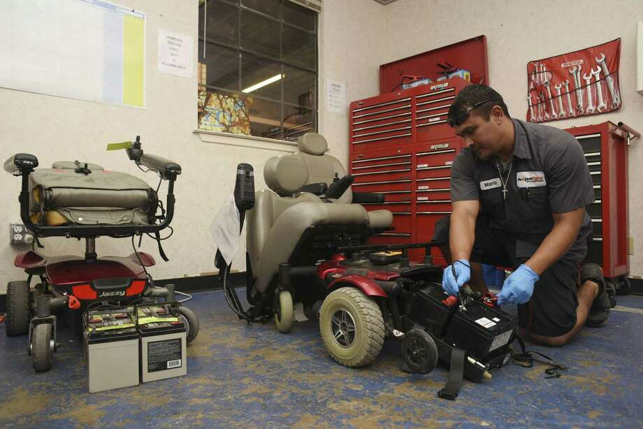 Mario Ochoa works on a donated power chair at Project MEND last year. Project MEND provides refurbished medical equipment and assistive technology to people with disabilities. Photo: Staff File Photo / San Antonio Express-News