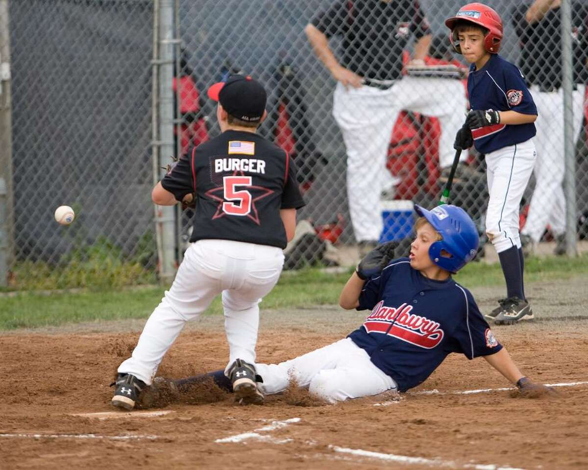 Danbury's Timmy MacDonald scores on a wild pitch as New Canaan's pitcher Matt Burger waits for the ball during the Cal Ripken 10-year-old state tournament first round game Saturday night at Rogers Park.