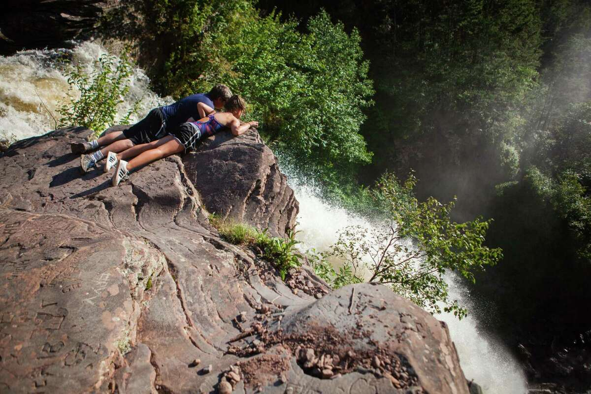 Visitors come recklessly close to the edge of the Kaaterskill Falls, in Hunter, N.Y., Aug. 6, 2018. The last four people who died at Kaaterskill Falls in the Catskills were taking or posing for pictures, according to a New York forest ranger. Now the state is taking steps to make the site safer. (Piotr Redlinski/The New York Times)