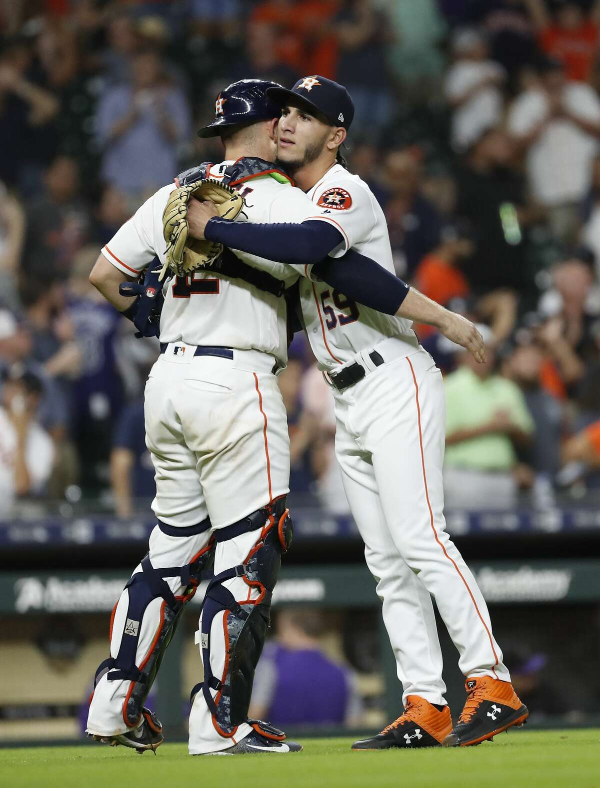 Houston Astros relief pitcher Cionel Perez (59) hugs catcher Max Stassi (12) after the Astros beat Colorado Rockies 12-1 during an MLB game at Minute Maid Park, Wedneaday, August 15, 2018, in Houston.