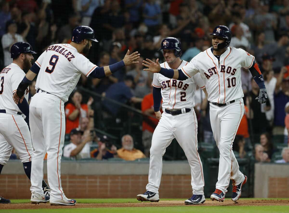 Houston Astros Yuli Gurriel (10) and Alex Bregman (2) and Marwin Gonzalez (9) celebrate their runs scored on Carlos Correa's RBI double during the first inning of an MLB game at Minute Maid Park, Wedneaday, August 15, 2018, in Houston.