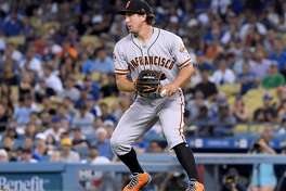 LOS ANGELES, CA - AUGUST 15: Derek Holland #45 of the San Francisco Giants looks back Enrique Hernandez #14 of the Los Angeles Dodgers, after fielding a groundball off the bat of Yasiel Puig #66 at second base during the second inning at Dodger Stadium on August 15, 2018 in Los Angeles, California. (Photo by Harry How/Getty Images)