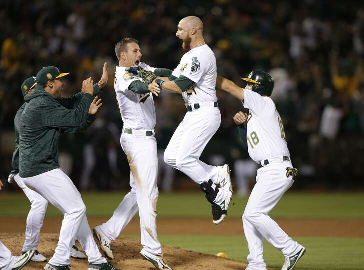 A's players, including a leaping Jonathan Lucroy, celebrate after beating the Giants in the 11th inning at the Oakland Coliseum on Saturday, July 21, 2018.