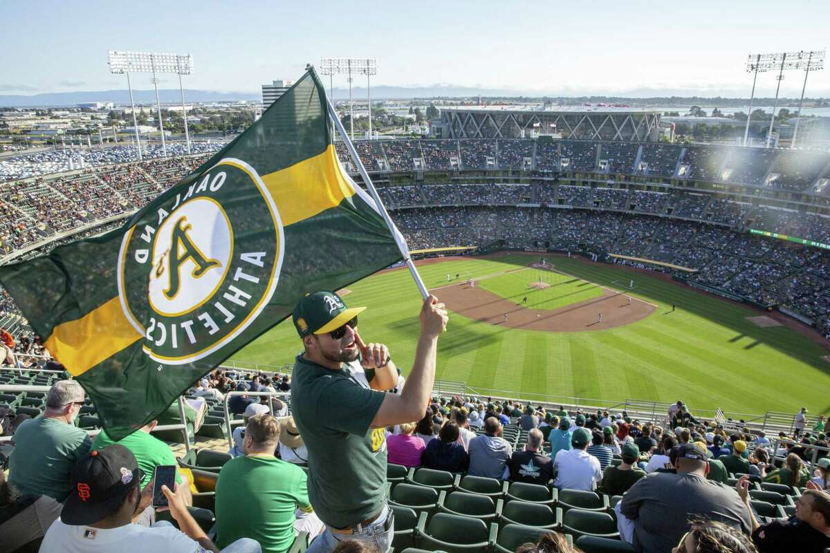 Juan Contreras of Stockton waves an Oakland A's flag at the top of Oakland Coliseum's Mount Davis during an MLB game between the A's and the San Francisco Giants on Saturday, July 21, 2018, in Oakland, Calif. For the first time in 13 years, the A's opened Mount Davis, the tallest deck in the Oakland Coliseum.