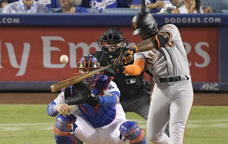 San Francisco Giants' Andrew McCutchen hits a three-run home run as Los Angeles Dodgers catcher Yasmani Grandal and home plate umpire Stu Scheurwater watch during the eighth inning of a baseball game Wednesday, Aug. 15, 2018, in Los Angeles. (AP Photo/Mark J. Terrill)
