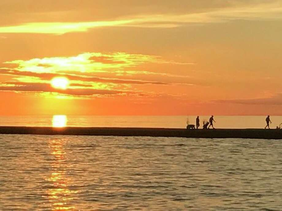 Michigan Outdoor Writers Association awarded Steve Griffin second place in color photography for this iPhone-captured scene of anglers at sunset leaving the pier at Ferrysburg on the Grand River, where it flows into Lake Michigan between that village and Grand Haven. The photo was published in July 2017. (Steve Griffin/Midland Daily News file)