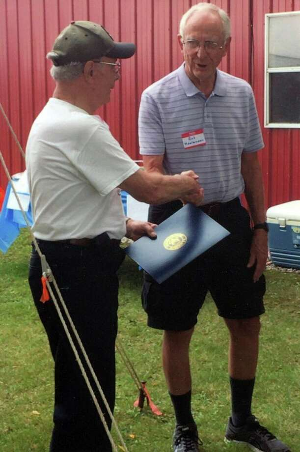 Rollin Yeakle, a grandson of William Yeakle, receives a special certificate honoring the Yeakle Centennial Farm from U.S. Rep. John Moolenaar, presented by his father, Bob Moolenaar.