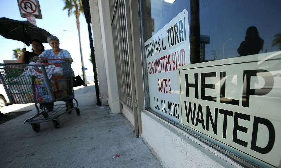 "Two women walk past a beauty salon with a ""Help Wanted"" sign in the window, in East Los Angeles, California on September 3, 2010. A better-than-expected report on employment September 3 was the latest piece of improving news on the economy.  The Labor Department said companies added 67,000 jobs in August, more than analysts expected.  AFP PHOTO / Robyn Beck (Photo credit should read ROBYN BECK/AFP/Getty Images) Photo: ROBYN BECK, AFP/Getty Images"