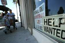 "Two women walk past a beauty salon with a ""Help Wanted"" sign in the window, in East Los Angeles, California on September 3, 2010. A better-than-expected report on employment September 3 was the latest piece of improving news on the economy. The Labor Department said companies added 67,000 jobs in August, more than analysts expected. AFP PHOTO / Robyn Beck (Photo credit should read ROBYN BECK/AFP/Getty Images)"