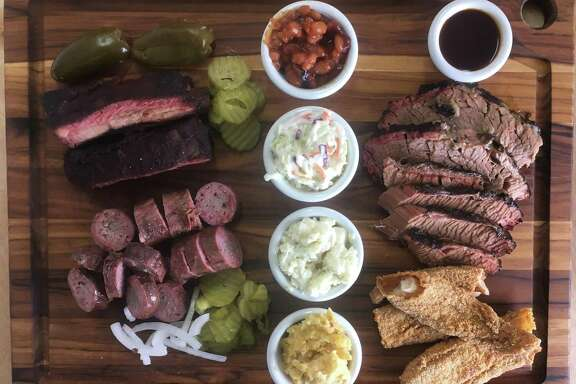 The board at 2 Sawers BBQ includes (clockwise from top left) St. Louis-style pork ribs, baked beans, marbled and lean brisket, fried catfish, corn spoonbread, potato salad, coleslaw and house beef sausage.