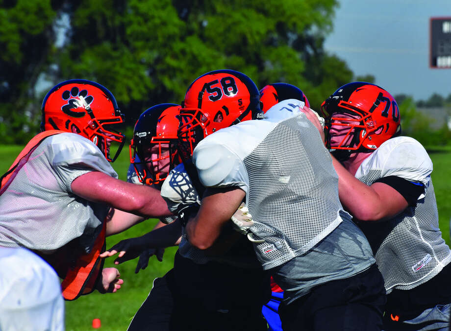 Members of the Edwardsville offensive and defensive lines battle each other during a practice at the District 7 Sports Complex. Photo: Matthew Kamp