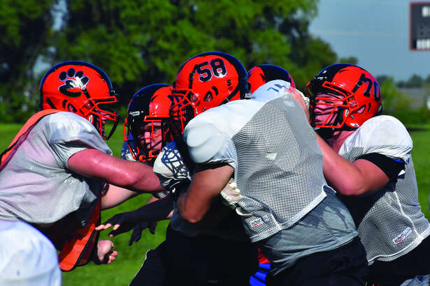 Members of the Edwardsville offensive and defensive lines battle each other during a practice at the District 7 Sports Complex.