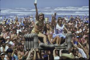 Crowd of college students on beach during spring break holding couch in the air on which bikini-clad girls sit.  (Photo by Shelly Katz/The LIFE Images Collection/Getty Images)