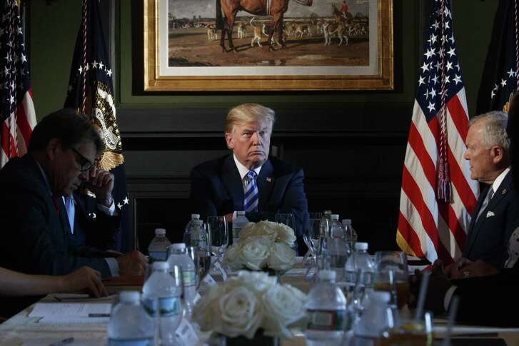 Energy Secretary Rick Perry has succeeded in Washington, in part by leaving the limelight to President Donald Trump. Here, Trump hosts state leaders for a discussion on prison policy at his golf resort in Bedminster, N.J., Aug. 9, 2018. Trump is in the midst of a long working vacation with few public appearances scheduled. At left is Perry, a former Texas governor; at right is Gov. Nathan Deal of Georgia