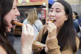 Lauren Camacho of San Francisco eats lumpia while attending the Undiscovered Creative Night Market hosted by SOMA Pilipinas in the South of Market district of San Francisco, Calif. Saturday, July 21, 2018.