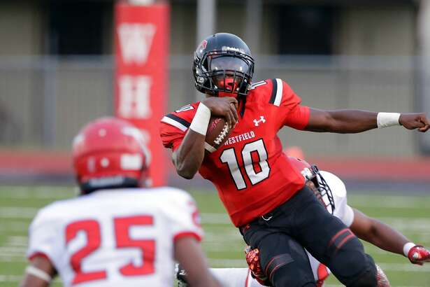 Westfield quarterback Terrance Gipson looks for a hole between North Shore's Drevian Williams-Nelson (25) and Jordan Revels in the first half of their game at George Stadium in Spring, TX, Sept. 15, 2017. (Michael Wyke / For the Chronicle)