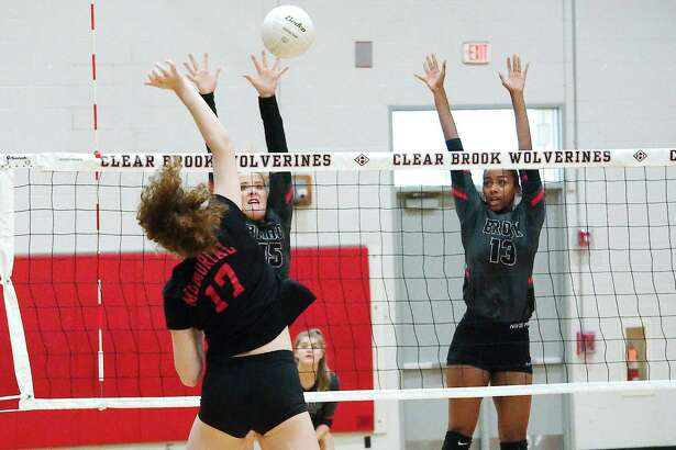Clear Brook's Mayce Barker (15) and Kennedy Crutchfield (13) go high to block a shot by Houston Memorial's Lyla Traylor (17) Tuesday in a non-district match.