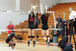 Clear Brook's Kailin Newsome (5) tries to hit a shot past Memorial's Caroline Isaac (20) and Lyla Traylor (17) Tuesday night. Newsome finished with a match-high 25 kills.
