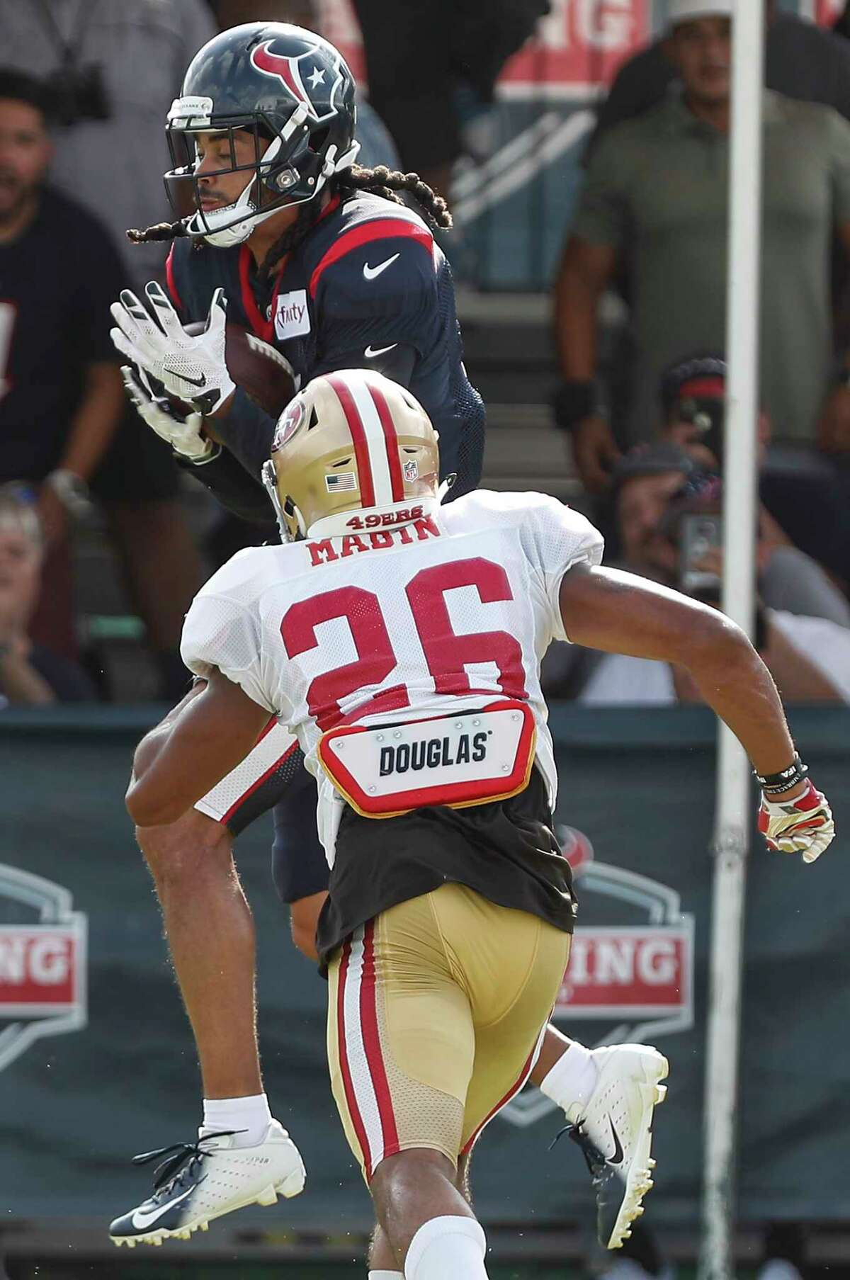 Houston Texans wide receiver Will Fuller (15) makeas catch over San Francisco 49ers cornerback Greg Mabin (26) during a joint practice between the Texans and 49ers at the Methodist Training Center on Thursday, Aug. 16, 2018, in Houston.