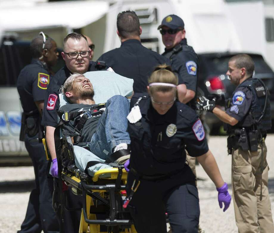 The suspect, Forest Hugh Olive, is transported by Montgomery County Hospital District paramedics at the scene where a car chase ended and two suspects were held at gunpoint by law enforcement at Omega Farms RV Park outside of Willis city limits on Wednesday, Aug. 15, 2018, in Conroe. The second suspect was later released with no charges filed against him. Photo: Jason Fochtman, Staff Photographer / Staff Photographer / © 2018 Houston Chronicle