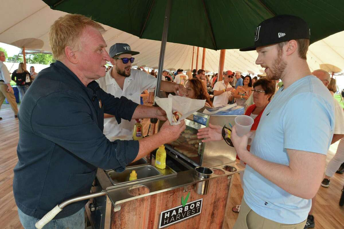 Harbor Harvest owner Bob Kunkel passes out house made beef hot dogs to Patrick Kennedy at the inaugural Taste of East Norwalk in August 2017. The festival returns on Sunday, Aug. 19.