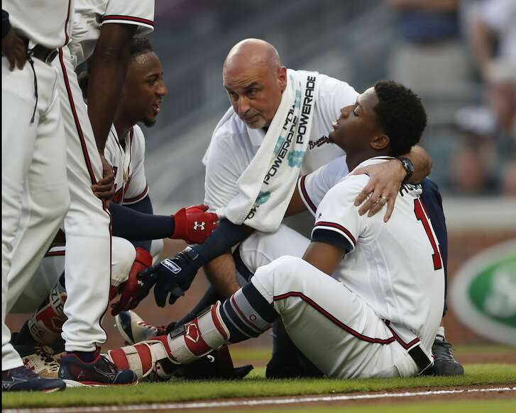 Atlanta Braves' Ronald Acuna Jr. (13) is tended to by a member of the training staff as Ozzie Albies talks to him after Acuna was hit by a pitch from Miami Marlins starting pitcher Jose Urena during the first inning of a baseball game Wednesday, Aug. 15, 2018, in Atlanta. (AP Photo/John Bazemore)