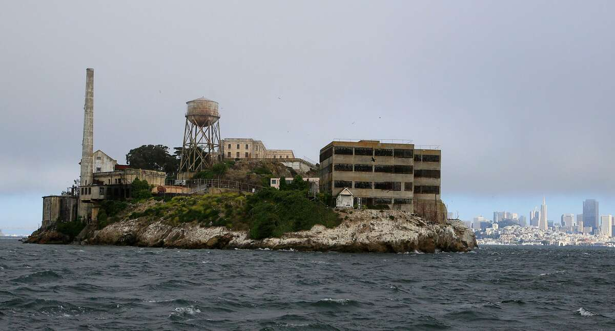 In this photo taken Thursday July 7, 2011, visitors get a rare view from a tour boat of the west side of Alcatraz Island before taking the night tour of the former prison in San Francisco. Most of the more than one million tourists who visit the famous former prison never get to experience Alcatraz at night or see its spooky, decrepit hospital unique to the night tour. At dusk the island prison that housed some of the nation's most notorious criminals including James Whitey Bulger and Al Capone is often covered in fog, and the lamps on the grounds emit a ghostly glow. (AP Photo/Eric Risberg)