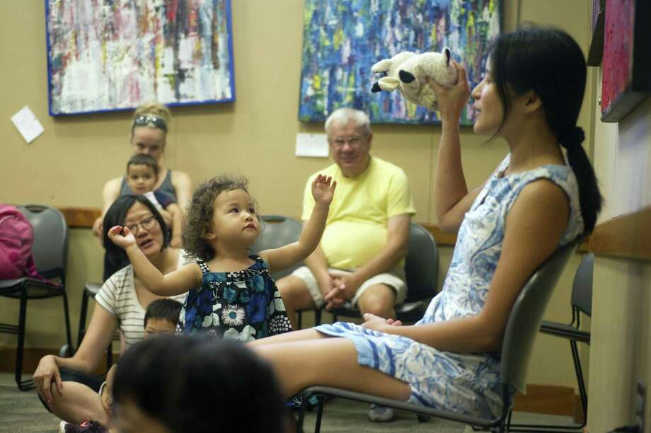 Two-year-old Sky reaches for a sheep puppet as Irene Ng leads a free children's class in Mandarin inside the Cos Cob Library in Greenwich, Conn. on Thursday, Aug. 9, 2018. Photo: Michael Cummo / Hearst Connecticut Media / Stamford Advocate