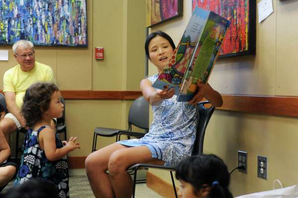 Irene Ng, right, reads a colorful book in Mandarin under the watchful eye of two-year-old Sky during free children's class inside the Cos Cob Library in Greenwich, Conn. on Thursday, Aug. 9, 2018.