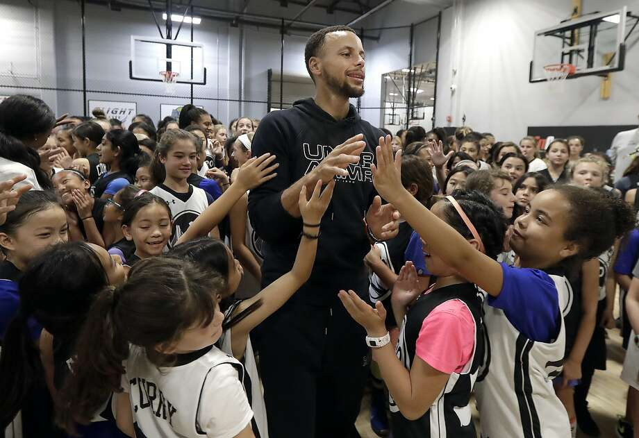 "Golden State Warriors' Stephen Curry, center, greets basketball camp participants after taking a group photo at Ultimate Fieldhouse in Walnut Creek, Calif., Tuesday, Aug. 14, 2018. For the first time, Curry hosted only girls for a free, Warriors-run camp Monday and Tuesday at Walnut Creek's Ultimate Fieldhouse. Last week at the same facility that he has also chosen in recent years, the Golden State star held his Under Armour ""Stephen Curry Select Camp"" with two of the nation's top high school girls playing mixed right in with the best boys. The two-time MVP and father of two young daughters has made it his mission to better support the girls' game. He asked longtime Warriors camp director Jeff Addiego to plan an all-girls session this summer. (AP Photo/Jeff Chiu) Photo: Jeff Chiu / Associated Press"