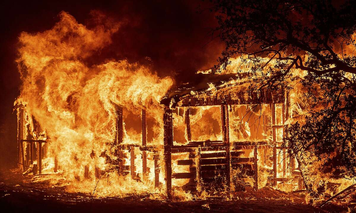 FILE--In this July 26, 2018, file photo, a structure burns as the Carr Fire races along Highway 299 near Redding, Calif. Redding firefighter Jeremy Stoke died after he was enveloped in seconds by a fire tornado with a diameter of 1,000 feet (300 meters) and winds up to 165 mph (265 kph), the California Department of Forestry and Fire Protection said in a report released Wednesday, Aug. 15, 2018, detailing his death and the death of a bulldozer operator. (AP Photo/Noah Berger, file)