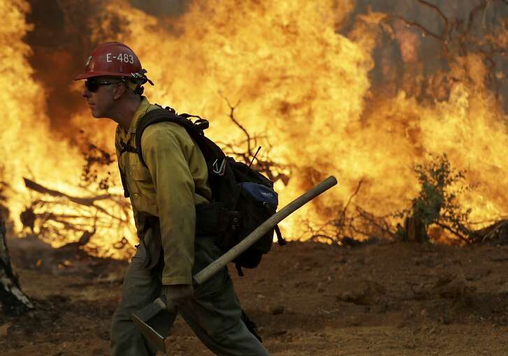 FIE--In this July 28, 2018, file photo, a firefighter walks along a containment line in front of the advancing Carr Fire in Redding, Calif. Redding firefighter Jeremy Stoke died after he was enveloped in seconds by a fire tornado with a diameter of 1,000 feet (300 meters) and winds up to 165 mph (265 kph), the California Department of Forestry and Fire Protection said in a report released Wednesday, Aug. 15, 2018, detailing his death and the death of a bulldozer operator. (AP Photo/Marcio Jose Sanchez, file)