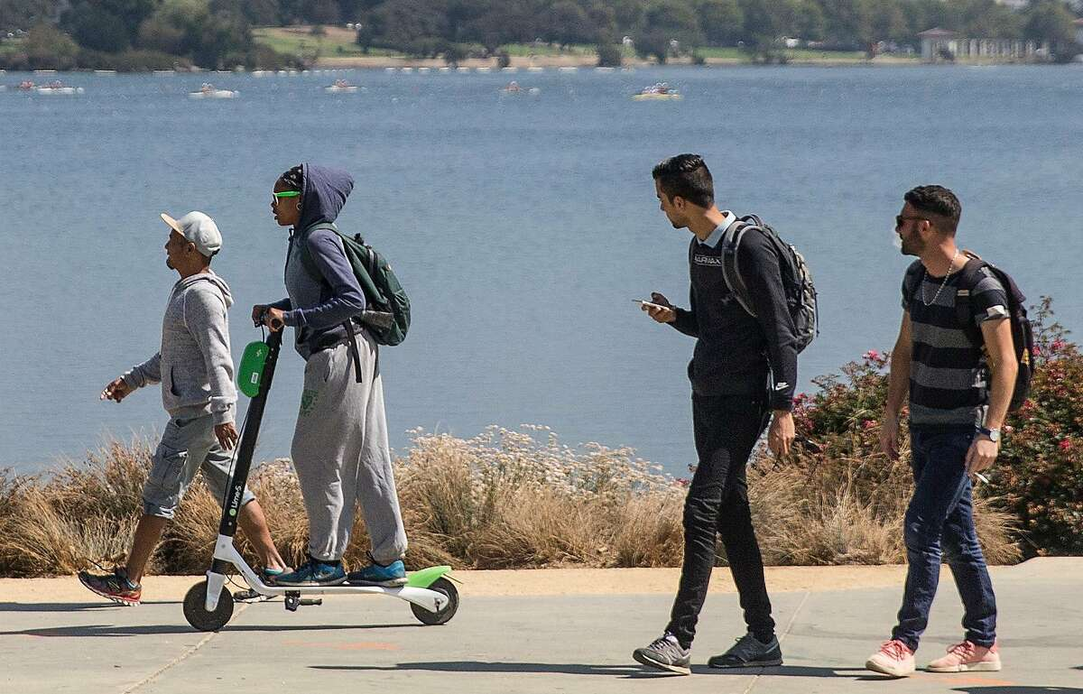 A woman rides a Lime electric scooter around Lake Merritt in Oakland, Calif. Thursday, Aug. 16, 2018.