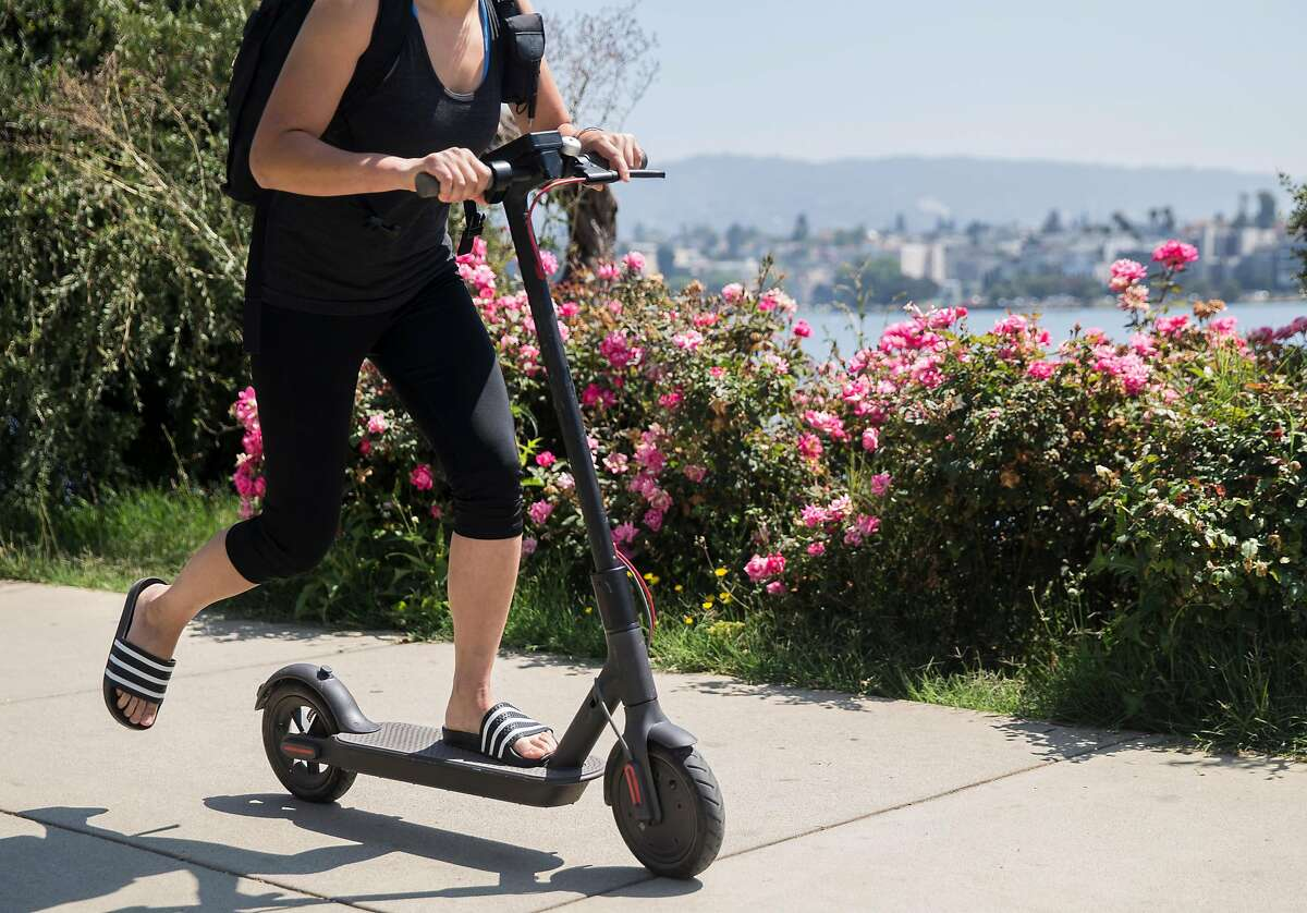 Brooke Sullivan rides a Bird electric scooter around Lake Merritt in Oakland, Calif. Thursday, Aug. 16, 2018.