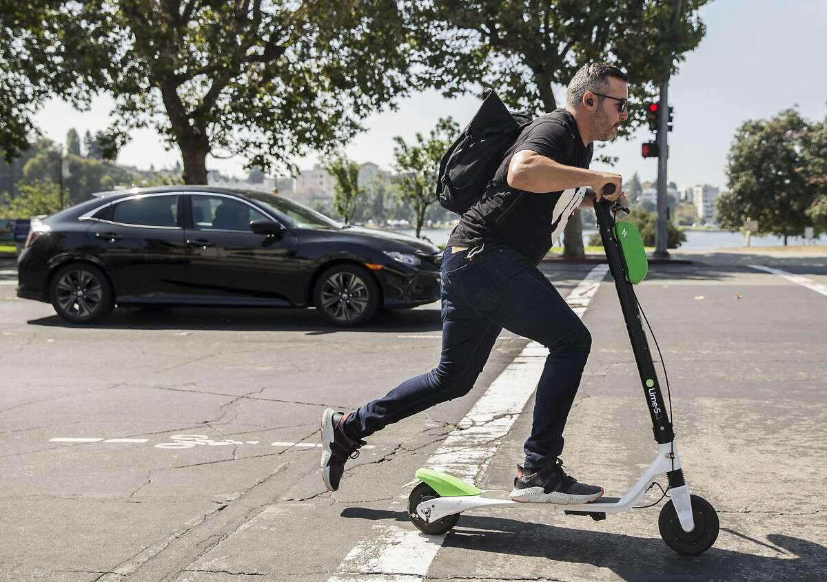 A man zips down Grand Avenue on a Lime electric scooter near Lake Merritt in Oakland, Calif. Thursday, Aug. 16, 2018.